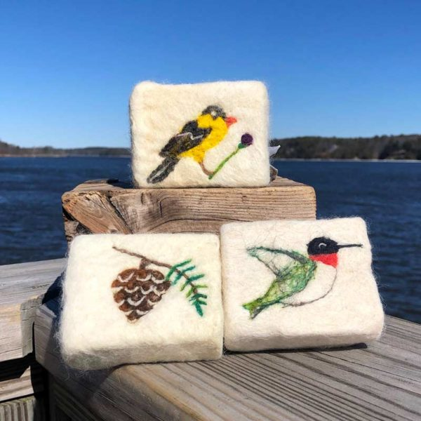 Alpaca Fleece, Felted Soaps with goldfinch, pinecone and hummingbird, sitting on a deck by the ocean.