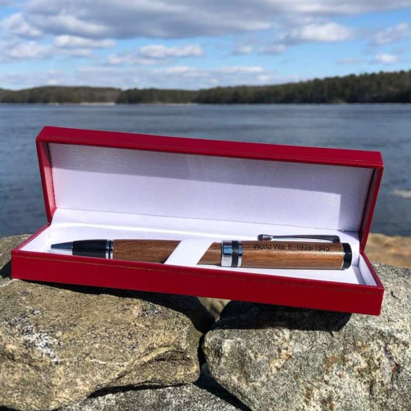 World War II Pen made from teak that was removed during the restoration of the Battleship North Carolina. It is laying in a red box by the ocean.