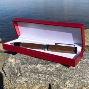 World War II Pen, made from teak that was removed during the restoration of the Battleship North Carolina. It is laying in a red box by the ocean.